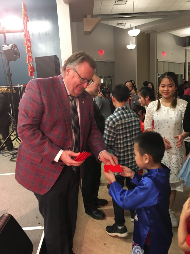 HANDING OUT LUCKY POCKETS AT THE SASKATOON VIETNAMESE NEW YEAR